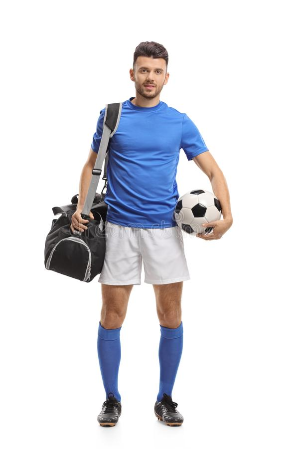 Soccer player with a sports bag and a football royalty free stock photo