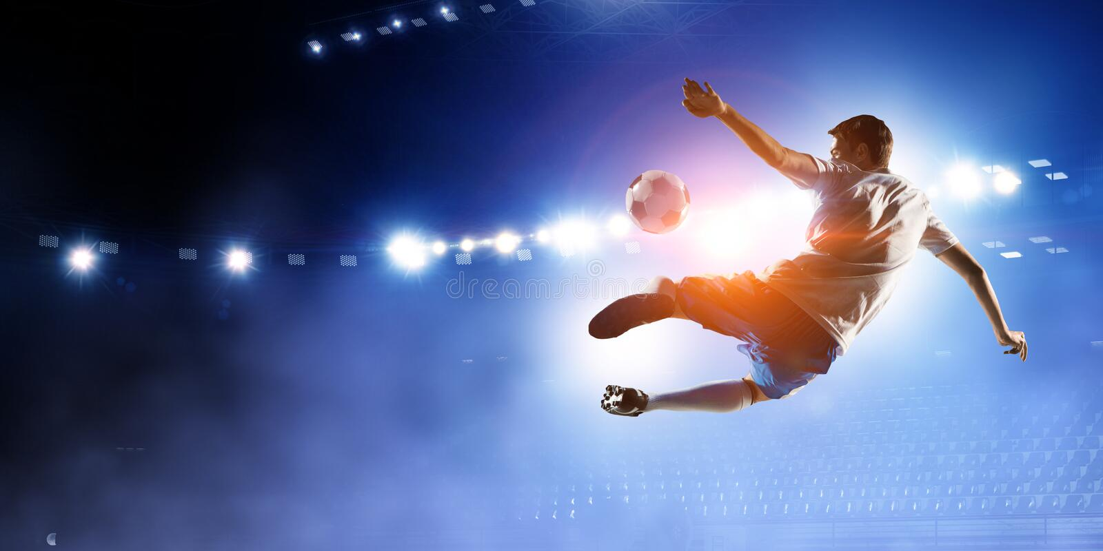 Soccer player on stadium in action. Mixed media royalty free stock photo