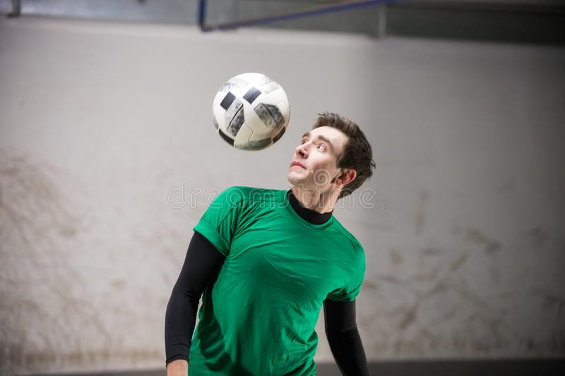 Soccer player training his skills with a ball. Mid shot royalty free stock image