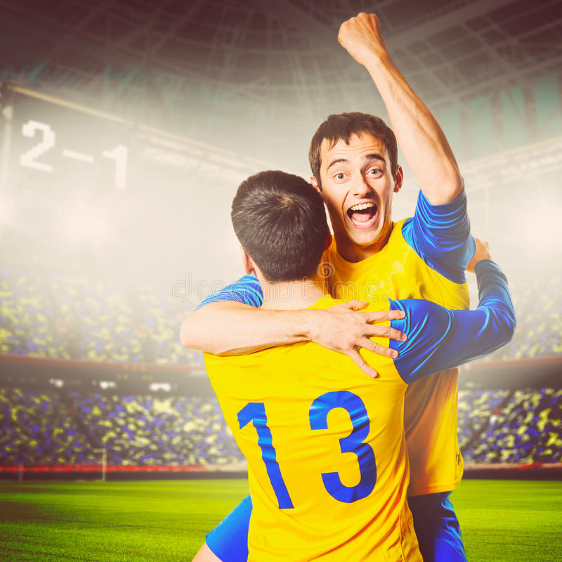 Soccer players. Soccer or football players are celebrating goal on stadium, warm colors toned royalty free stock photo