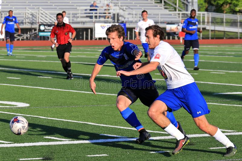 Soccer players chase the loose ball. Competitors race for the loose ball at the professional Soccer event, pro football game, NPSL, National Premier Soccer royalty free stock photos