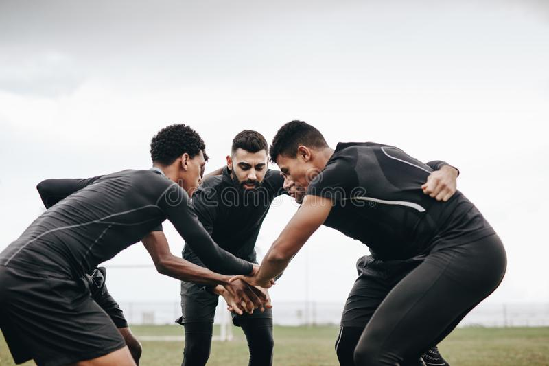 Football players standing in a huddle on the field stock images