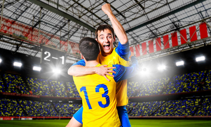 Soccer players. Soccer or football players are celebrating goal on stadium stock image