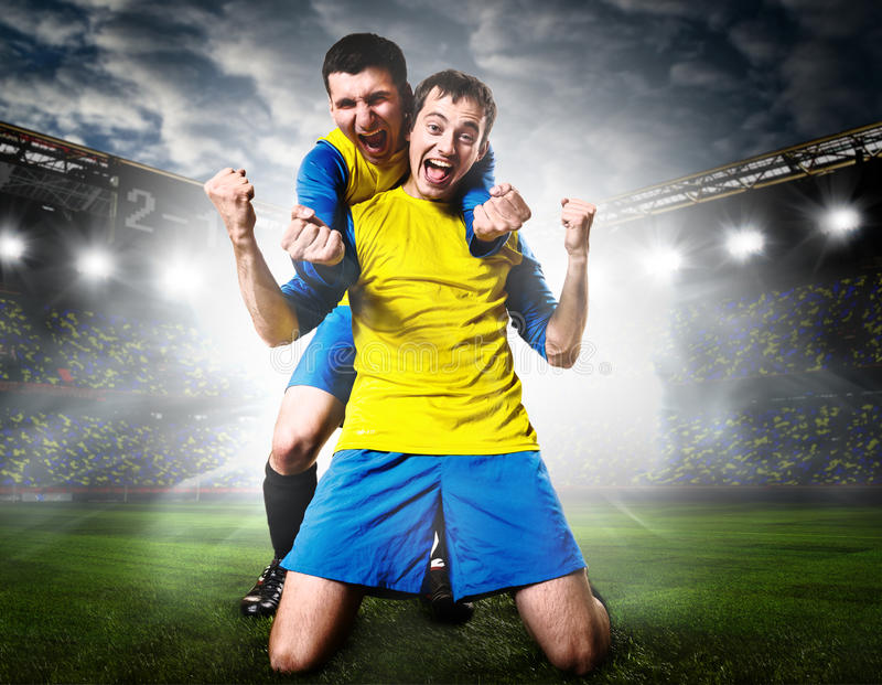 Soccer players. Soccer or football players are celebrating goal on stadium stock images