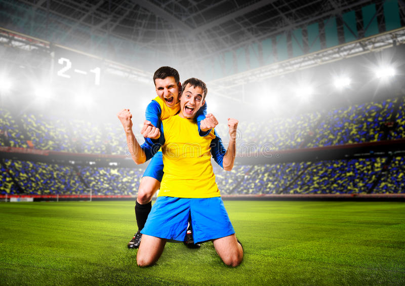 Soccer players. Soccer or football players are celebrating goal on stadium stock photo