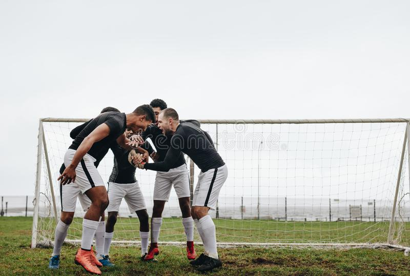 Soccer players joining hands standing in a huddle having a pep talk. Footballers cheering themselves up standing in a huddle on stock photos