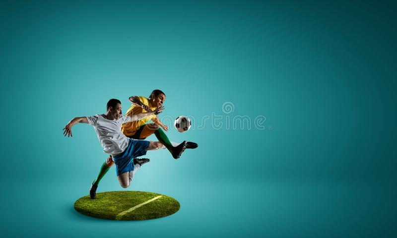 Soccer players on round pedestal. Mixed media. Two soccer players men on pedestal against color background. Mixed media stock photography