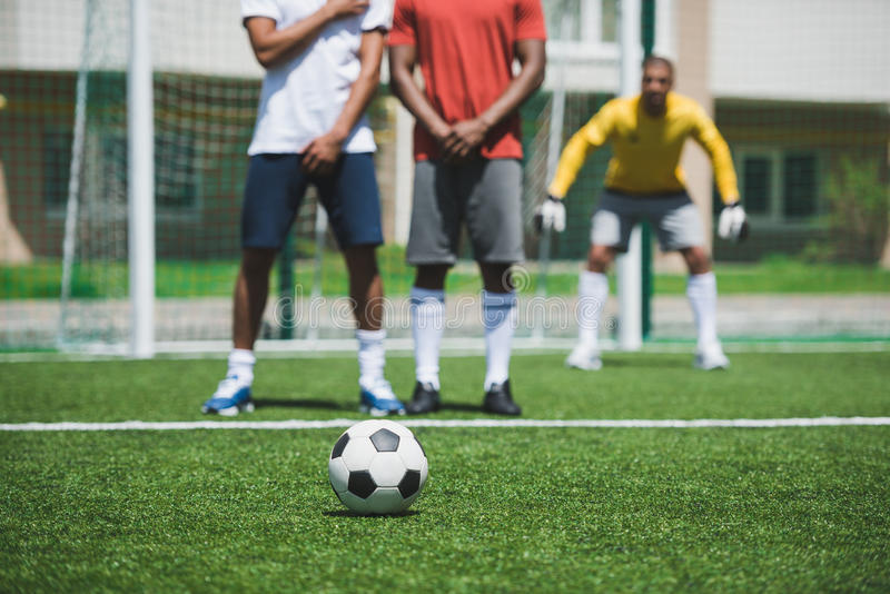 Soccer players during soccer match on pitch, focus on foreground stock images