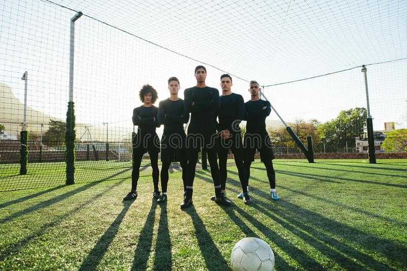 Soccer players standing together on pitch stock images