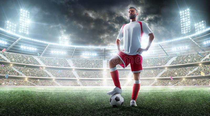 Soccer professional player preparing to the match. Foot on the soccer ball. Night Stadium background. Sport concept stock photography
