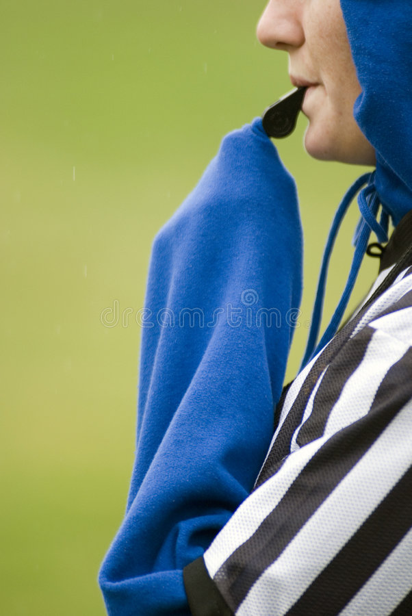 Soccer referee. Close up of referee blowing whistle stock images
