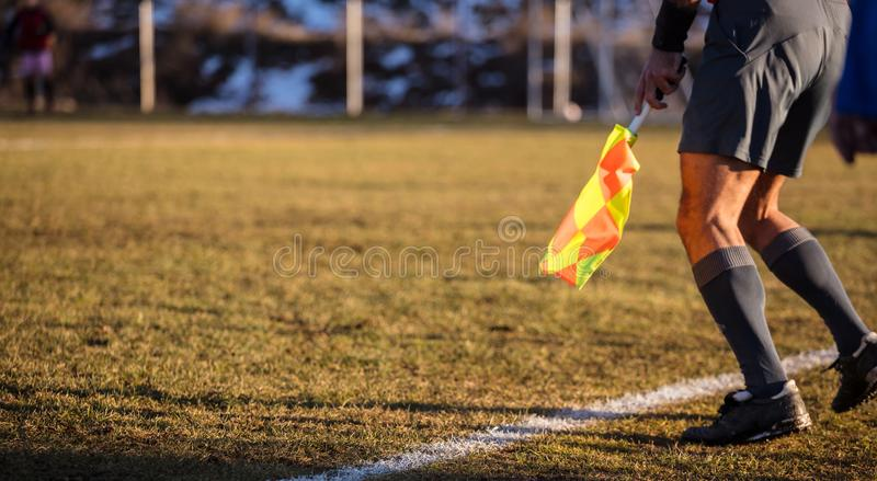 Soccer referee assistant moves at sideline with flag at hands. Blur green field,nature backdrop, close up view, banner, space. stock photo