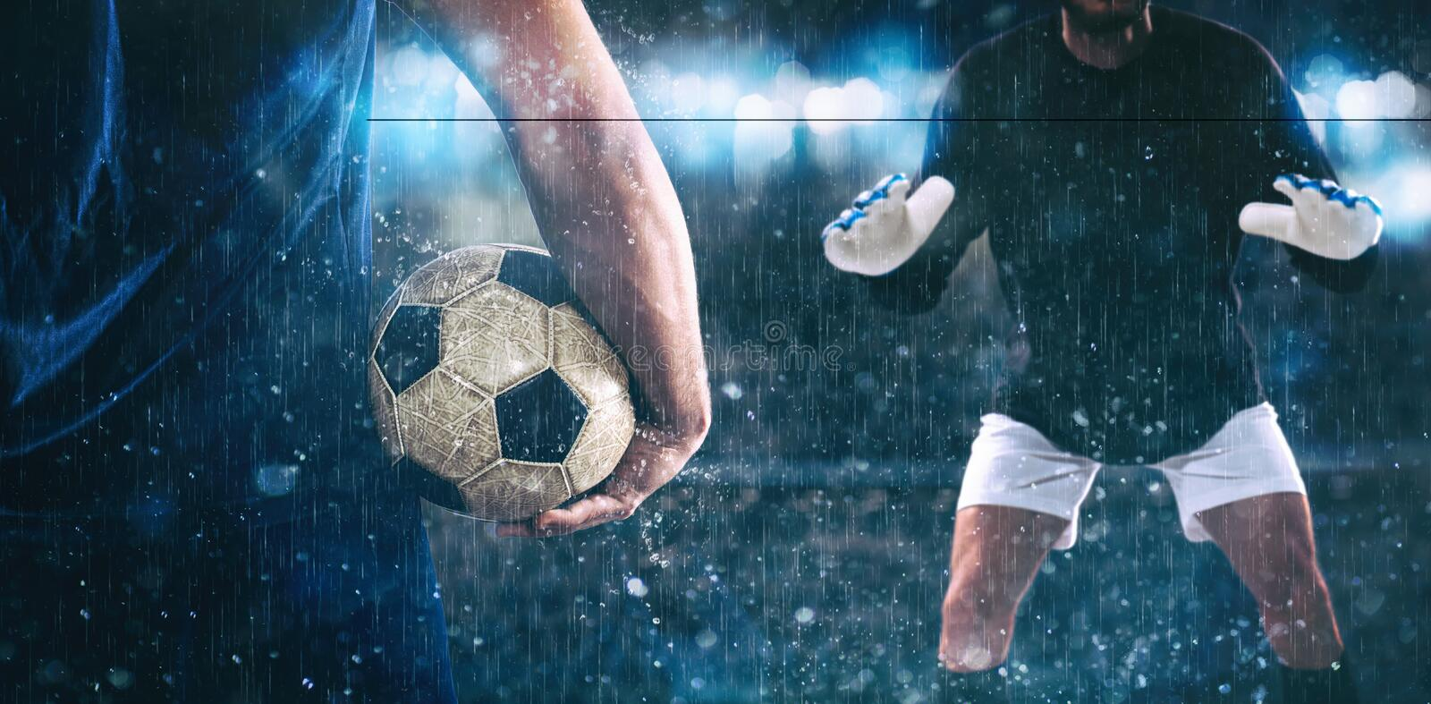 Soccer scene at night match with close up of a soccer striker holding the ball against the opposing goalkeeper. Challenge between the attacker and the goalkeeper royalty free stock photo