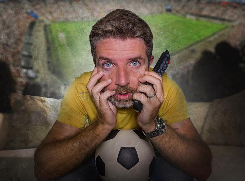 Soccer stadium composite with attractive and stressed man watching football game on TV at home couch excited in intense emotion. Enjoying the soccer match in royalty free stock images