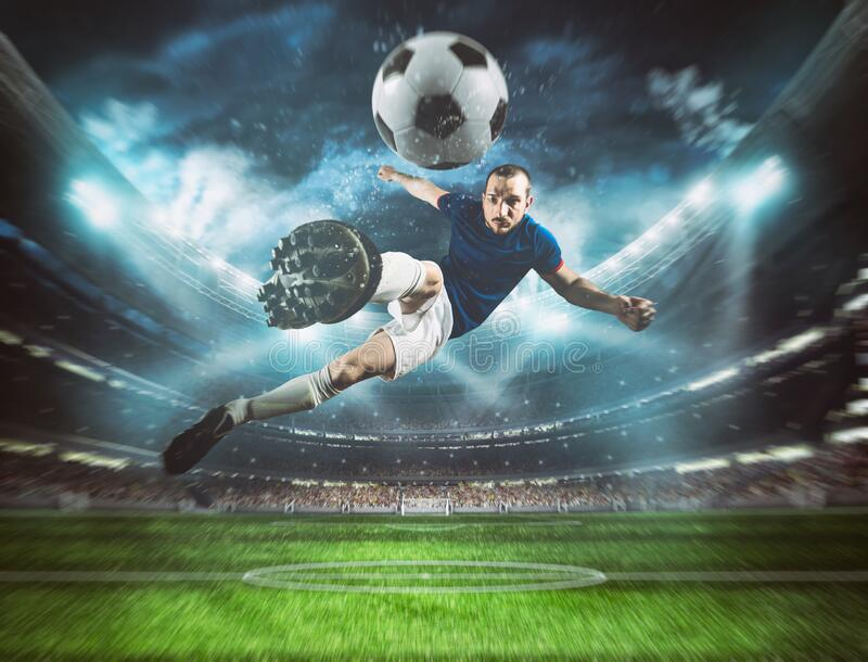 Soccer striker hits the ball with an acrobatic kick in the air at the stadium at night match royalty free stock photography