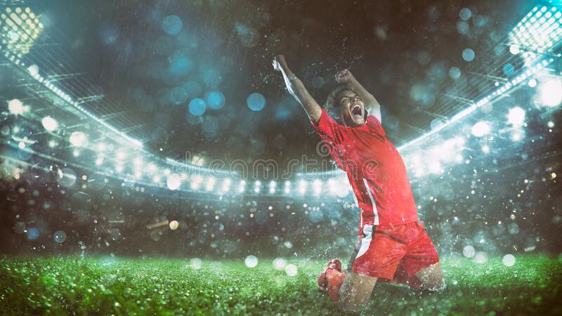 Soccer striker in red uniform rejoices for the victory at the stadium stock images