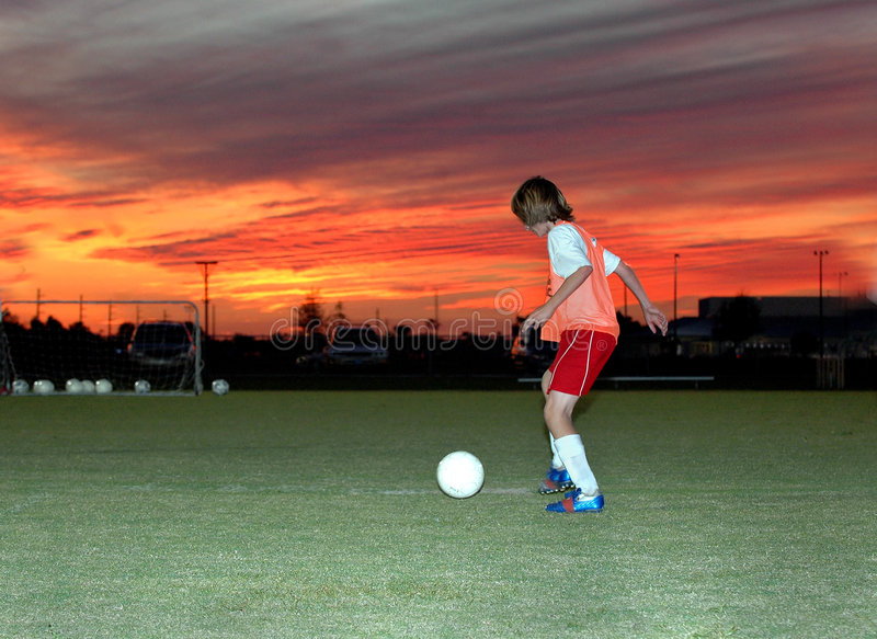 Soccer at sunset. A boy practicing soccer under a red sunset sky