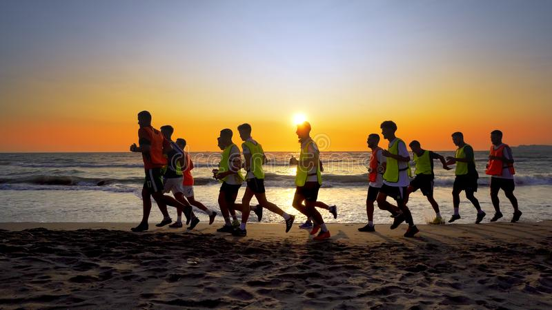 The soccer team, coaching training running outdoor under the beach sunset stock photo