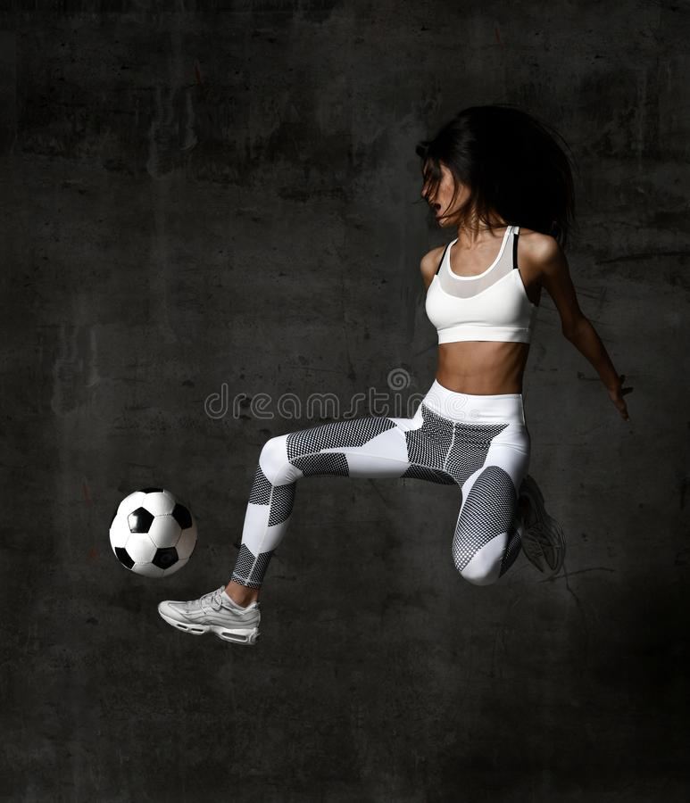 Soccer woman player jumps and hit the ball strike in the middle on concrete loft wall stock image