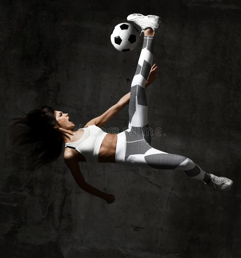 Soccer woman player jumps and hit the ball yelling screaming on concrete loft wall royalty free stock image
