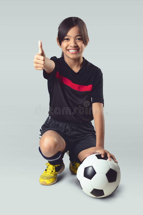 Soccer. Young asian girl holding soccer ball, Isolated over white stock photography