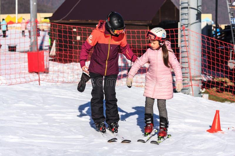 Sochi, Rússia - 7 de janeiro de 2018: O instrutor fêmea do esqui ensina o esqui à menina pequena na inclinação de montanha nevado imagens de stock royalty free