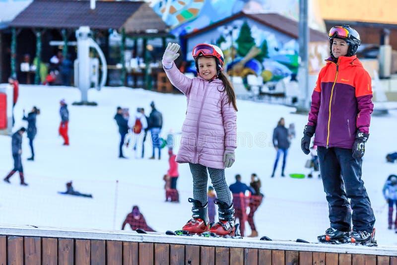 Sochi, Rússia - 7 de janeiro de 2018: O instrutor fêmea do esqui ensina o esqui à menina pequena na inclinação de montanha nevado imagem de stock royalty free