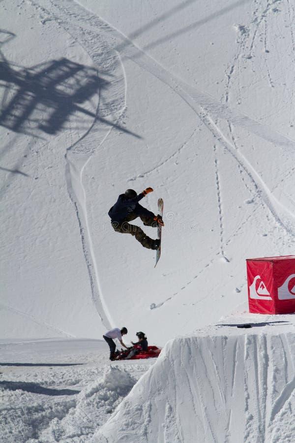 SOCHI, RÚSSIA - 22 DE MARÇO DE 2014: O Snowboarder salta no parque da neve, estância de esqui fotos de stock