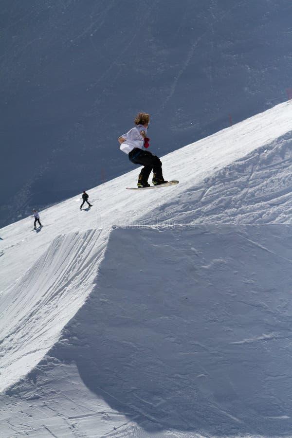 SOCHI, RÚSSIA - 22 DE MARÇO DE 2014: O Snowboarder salta no parque da neve, estância de esqui fotografia de stock royalty free