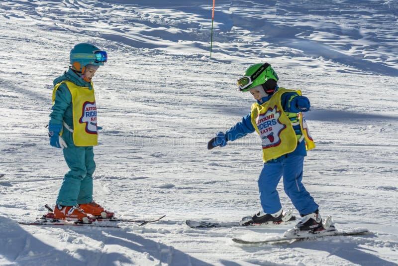 Sochi, Rússia, 10-01-2018 Estância de esqui de Rosa Khutor Um menino e uma menina de um grupo de trem do treinamento do esqui da  imagem de stock royalty free