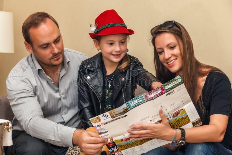 Sochi Rosja, Maj, - 30, 2014: Młoda szczęśliwa Kaukaska rodzina ojciec, matka i córka siedzi wpólnie i planuje wakacje, obrazy stock