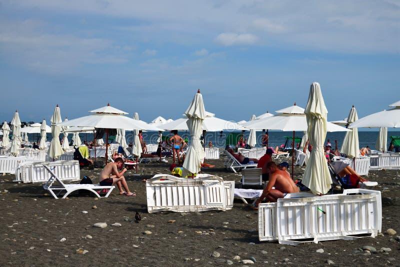 Sochi, Rusia - 5 de junio 2018 gente en la playa equipada de los paraguas y de los ociosos del sol imagenes de archivo