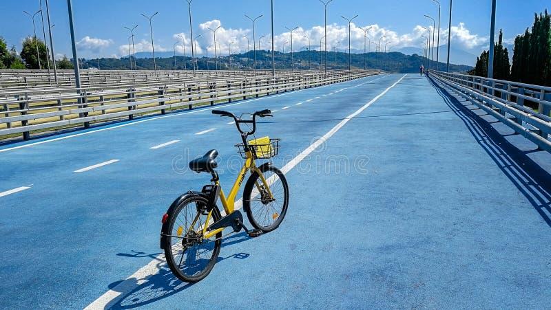 SOCHI, RUSIA - julio de 2019: Bici amarilla 'Mobee de alquiler ', camino azul al parque olímpico de Sochi imágenes de archivo libres de regalías