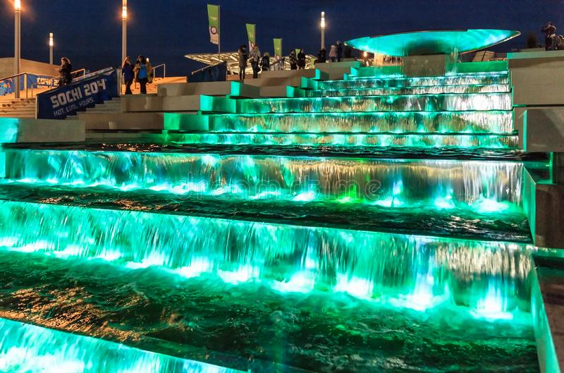 Illuminated waterfall fountain cascade by Olympic Park enchants with its beautiful play of. Sochi, Russia - February 10, 2014: Illuminated waterfall fountain stock image