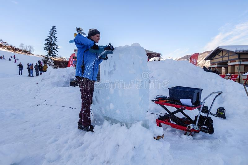 Sochi, Russia - January 24, 2015: Ice carving master making ice sculpture with electric chainsaw on snowy mountain slope of Gorky royalty free stock photos