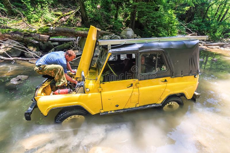 Off-road Russian car stuck in mountain river at sudden breakdown while jeeping. Driver fixing the auto with hood lifted up royalty free stock photos