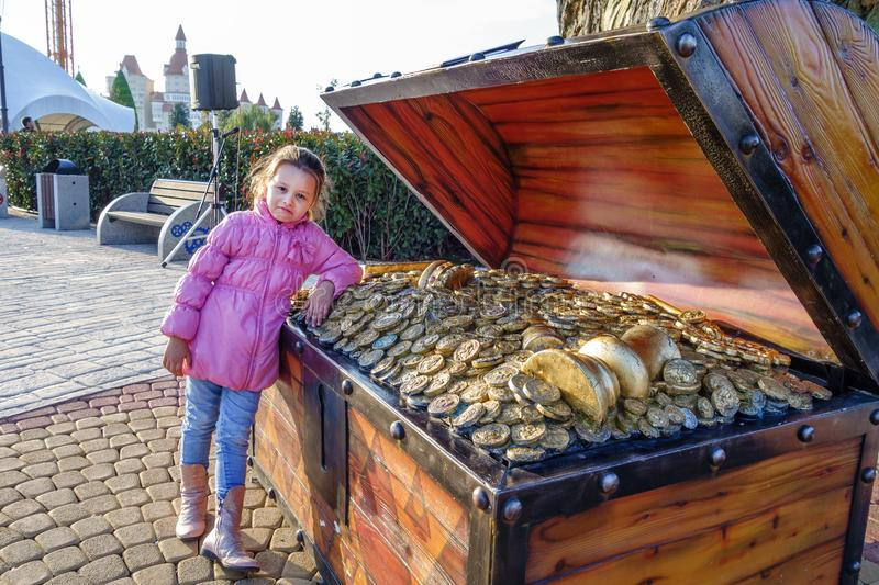 Small Caucasian girl standis beside artificial chest full of gold treasures in Sochi Park which is biggest and most amazing stock photos