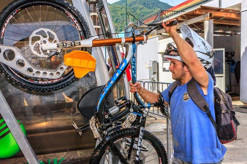 Sportsman biker fixes bicycle to cable car lift cabin in Gorky Gorod mountain ski resort to take bike ride in terrain bike park royalty free stock photography