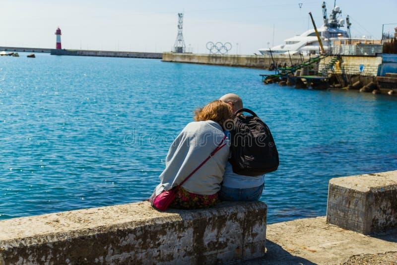 SOCHI, RUSSLAND, AM 23. APRIL 2019 - romantische Paare, die auf dem Strand, dem Mann und der Frau Schwarzen Meers sitzen zurück z lizenzfreie stockbilder