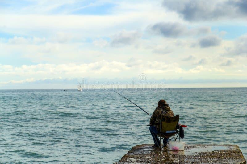 SOCHI RYSSLAND, 23 APRIL 2019 - en man som fiskar på Blacket Sea, en fiskare som sitter på en vågbrytare med en metspö på solnedg royaltyfria bilder