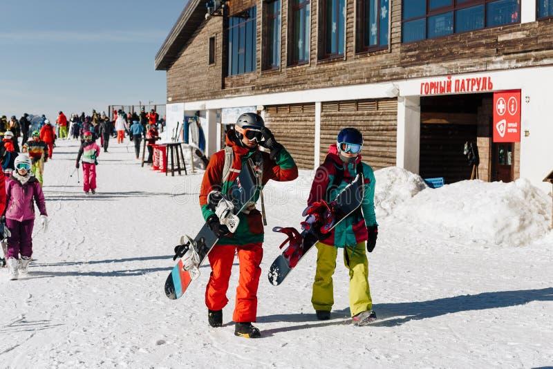 Sochi Ryssland - Januari, 2017 - barn kopplar ihop med snowboards i en skidasemesterort royaltyfria bilder