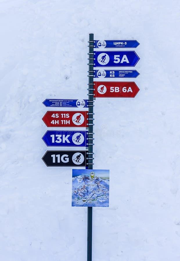 Sochi Ryssland - Januari 7, 2018: Pole med peka riktningar för färgrika informationspilar som skidar slingor av olik komplexitet  arkivfoton