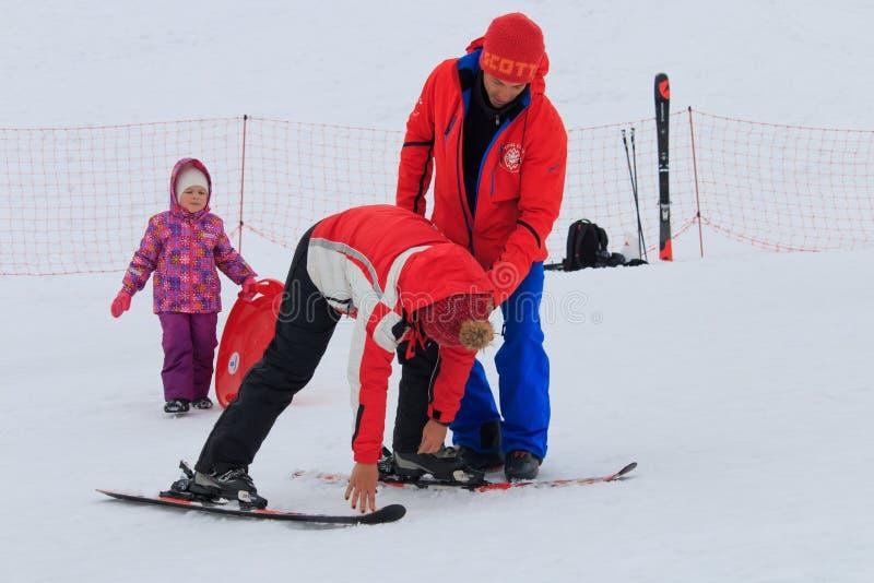 Sochi Ryssland - Januari, 2017: Ski Instructor undervisar unga flickan att stå på skidar royaltyfria bilder
