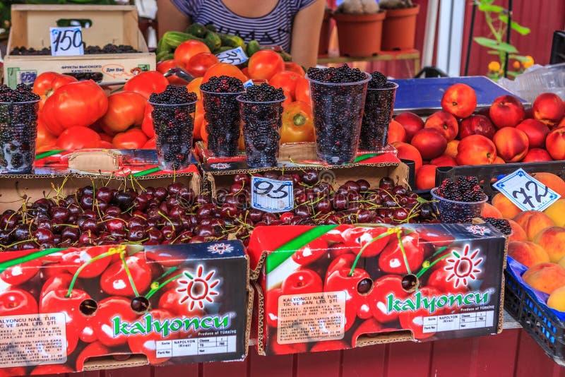 Sochi Ryssland - Juli 26, 2008: Olika mogna nya frukter och bär säljer på en gatamarknad Shopdoard sikt royaltyfria foton