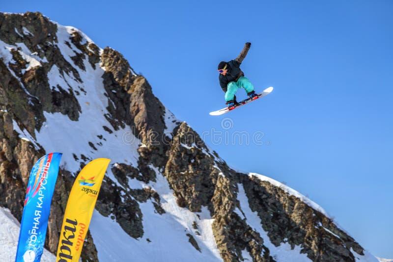 Sochi Ryssland - mars 25, 2014: Snowboarderen flyger i luft från stort lufthopp på bakgrund för blå himmel och berg arkivbild