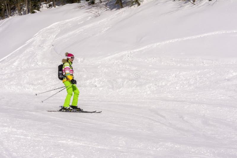 Sochi Ryssland, 11-01-2018 Rosa Khutor skidar semesterorten, flickaskidåkare i en ljus dräkt ner den snowny lutningen arkivbilder
