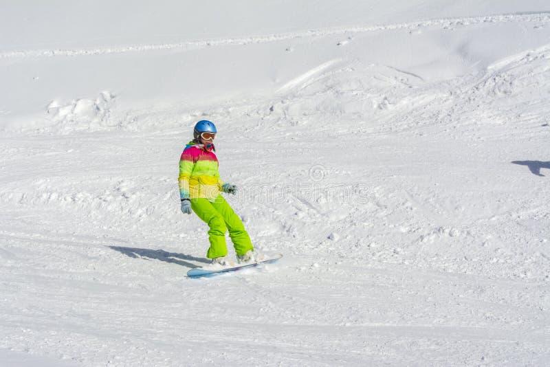 Sochi Ryssland, 11-01-2018 Rosa Khutor skidar semesterorten, flickaSnowboarder i ljusa dräkter överst av Rose Peak på en höjd av  royaltyfri foto
