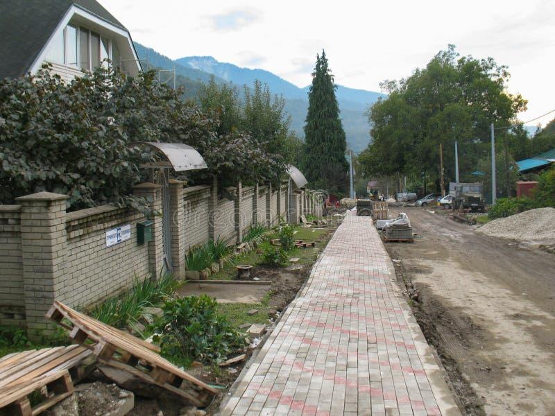 Sochi Ryssland - September, 2013: Vägreparation på den huvudsakliga gatan av den olympic byn i Krasnaya Polyana arkivbilder