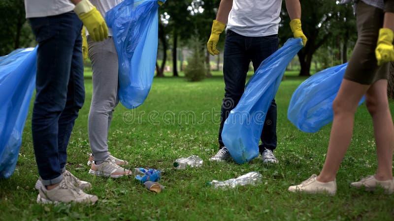 Société contre la pollution, citoyens actifs rassemblant des déchets en parc public image stock