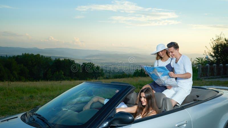 Société voyageant en voiture, couple se reposant sur le cabriolet et tenant la carte image libre de droits